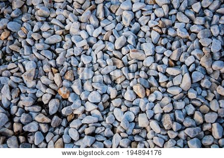 The background with brown yellow and grey small angular stones of different sizes and shapes with rough surface and inclusions of another colors. Flat view
