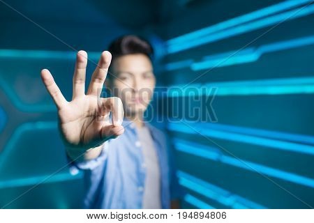 man smile happily and show ok to you on the technology background