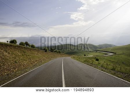 Smooth asphalt road to the mountains road to the distance beyond the horizon to the clouds