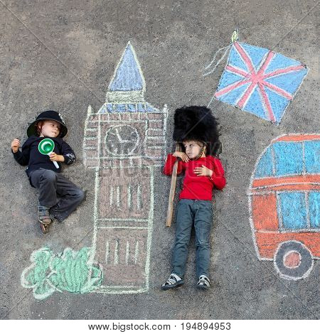 Two funny little friends boys in british queen's guard soldier and policeman uniform having fun with London picture drawing with colorful chalks. With Big Ben, Union Jack and red bus. Creative leisure with children.