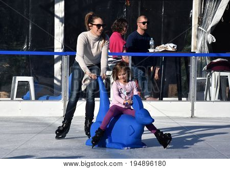 Sydney Australia - Jun 25 2017. Kids and parents ice skating at Hyde Park. Kids sitting on Kangaroo Skate Aid. The Winter Festival is Australia's winter events featuring open-air ice-skating.