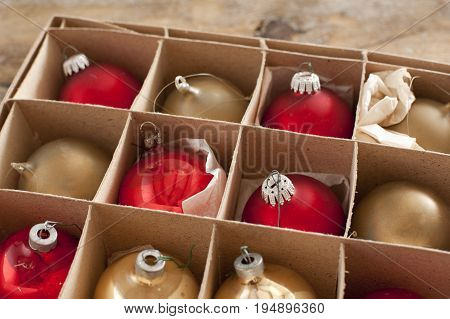 Cardboard box of colorful Christmas decorations with red and gold baubles or balls for the Xmas tree to celebrate the festive holiday season