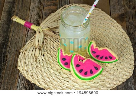 lemonade drink in mason jar with polka dot drinking straw and watermelon sugar cookies on tropical place mat