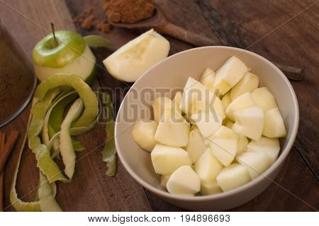 Preparing homemade apple sauce with peeled and diced fresh green cooking apples and ground aromatic cinnamon spice to serve as an accompaniment to meat