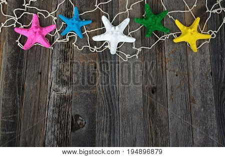 colorful starfish in nautical netting border on weathered wood