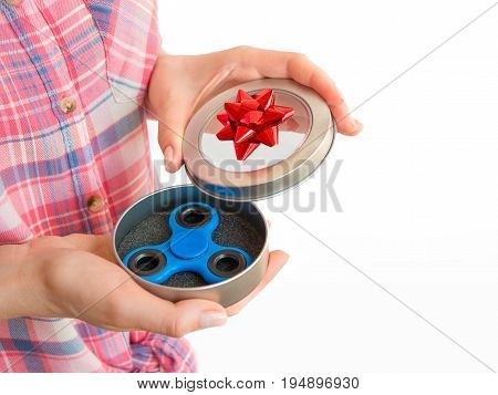 Girl holding a colourful hand fidget spinner toy in a gift box.