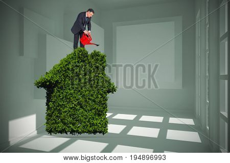 Mature businessman using watering can against white room with squares at wall