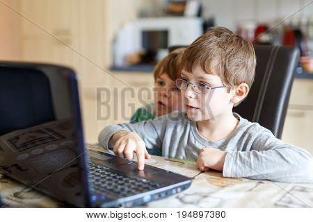 Two little kids boys surfing internet on computer. Children, siblings, friends and twins having fun with learning on pc. Education concept.