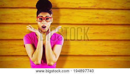 Portrait of surprised young woman standing  against full frame shot of orange wall