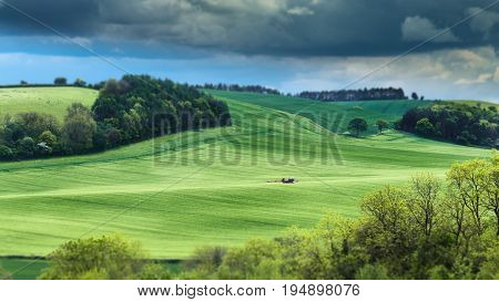 Agricultural Machine Spraying Pesticides on Green Wheat Hills