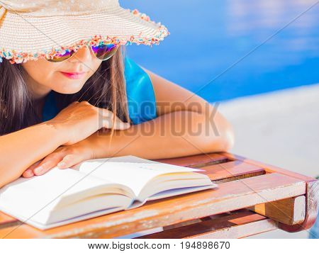Close up woman in summer hat lying on deckchair and reading a book by the swimming pool. Vacation and relaxation summer travel concept.