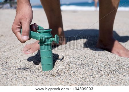 closeup of a young caucasian man installing the grabber of a beach umbrella in the sand of a beach