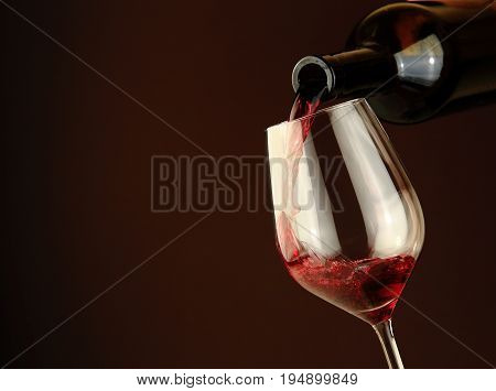 Wine splash in glass. Close-up of red wine pouring into wine glass. Alcoholic background.