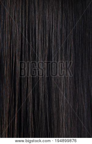 Long straight black hair. Dark woman hair texture. Black female hair background.
