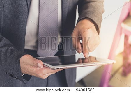 a Businessman is using a modern tablet.