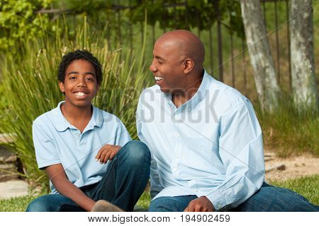 African American father and son talking outside.