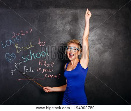 Young attractive student at the school board. She rejoices at the beginning of the school year and holds a pointer in her hands. Back to school. She welcomes new students.