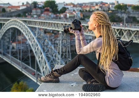 Young tourist woman with camera sitting on the viewing platform opposite the Dom Luis I bridge across the Douro river in Porto, Portugal.