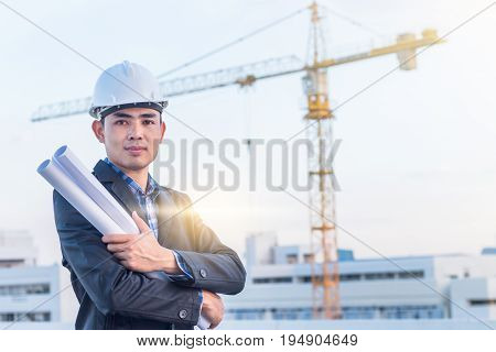 The architect wear white safety helmet and hold the blueprint with commitment on construction site with crane background