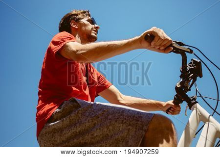 young man ride a bicycle from below shot hot summer day real people concept