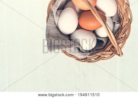 Basket with white and brown natural eggs on white wooden background