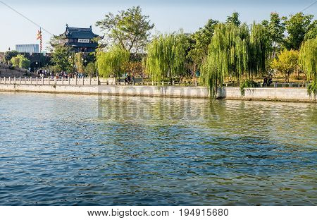 Suzhou, China - Nov 5, 2016: View of the tower building and Waicheng River as viewed from a nearby public park. A serene scene.