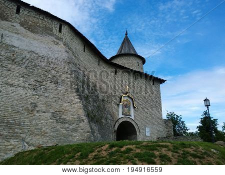 A high stone wall and tower of the Pskov Kremlin at the entrance to the territory