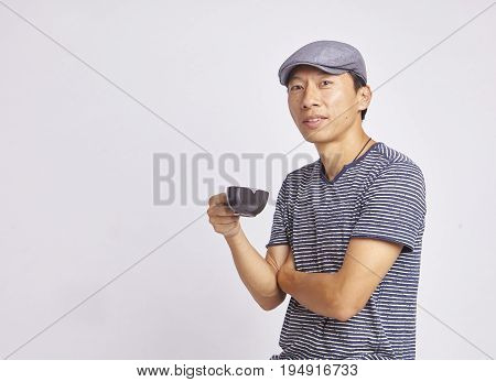 Asian Man Smiling At Camera Holding Coffee Cup Isolated