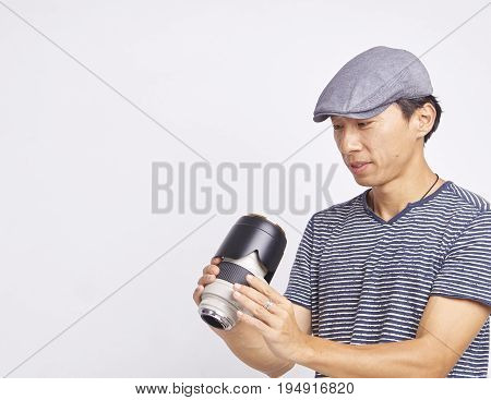 Asian Photographer Checking Lens Isolated On White