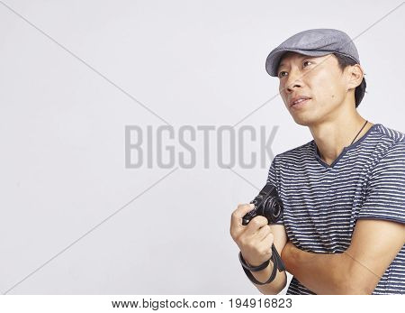 Asian photographer looking into distance isolated on white