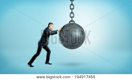 A businessman on blue background pushing at a hanging unmoving wrecking ball. Heavy burden. Impossible problems. Hard work for success.