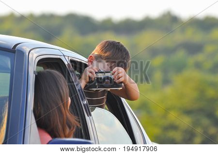 Boy Taking photo of his mom on start of journey. Travel concept. Happy family in the car.