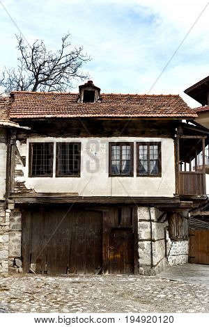 Old house stone paved road alley, wooden benches Bansko ski tourist centre of Bulgaria