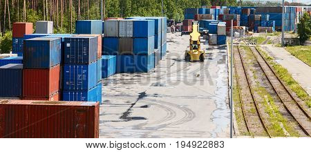 A container terminal. Small storage containers for rail and sea transport. Loader for containers. Metal box for cargo.
