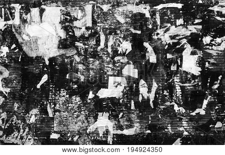 Grunge black and white texture. Old torn pieces of paper on the wall. Several layers of aged ragged papers.