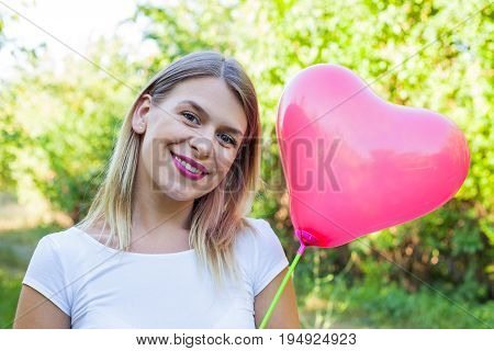 Portrait of a sexy young woman holding a heart shaped balloon posing outdoor on summertime
