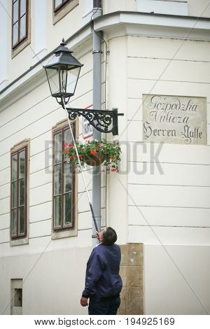 ZAGREB CROATIA - MAY 20 2017 : A street lamp lighter lighting up the gas street lamp on Gradec in Zagreb Croatia.