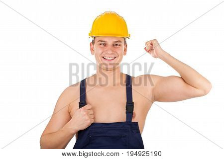 Picture of a shirtless young constructor wearing a yellow helmet and navy blue uniform on isolated background