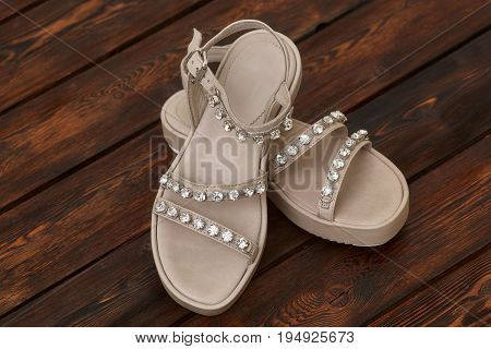 Pair of beige leather female sandals with rhinestones on wooden background