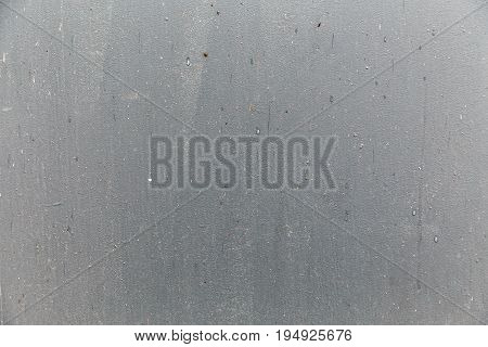 Texture of gray metal door painted unevenly with brush strokes and roughness on the surface.