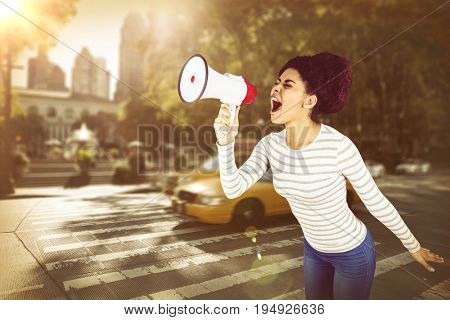 Carefree young woman yelling with megaphone  against picture of a zebra crossing