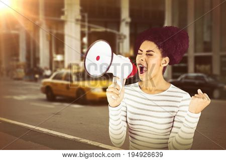 Excited woman shouting with megaphone  against picture of a city