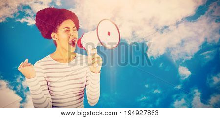 Excited woman shouting with megaphone  against view of beautiful sky and clouds