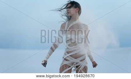 Girl in desert in image of Egyptian mummy with knife in her hand. She goes all wrapped in bandages and she has hieroglyphics on her body. Around her sand flies in the air.