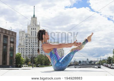 Exercises Yoga. Young beautiful woman doing yoga on the background of the city of Moscow (Russia)