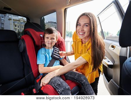 Wide shot of graceful mom checking son sitting in baby seat