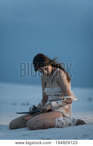 Girl in image of Egyptian mummy sits on sand with knife in her hand. She is wrapped in bandages and she has hieroglyphics on her body.