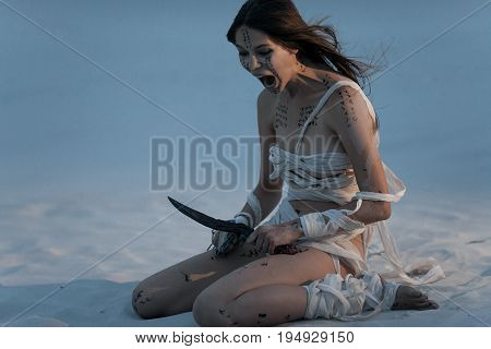 Girl in image of Egyptian mummy sits on sand with metal chain and knife in her hands and screams in fury. She is wrapped in bandages and she has hieroglyphics on her body.
