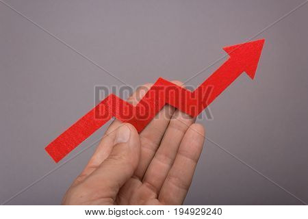 Graph chart growing up in the hand. Success is in your hands. Red arrow up in a man's hand on a gray background. Price increase