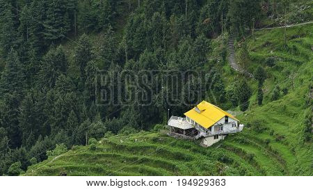 House with Yellow Roof Situated in Hills